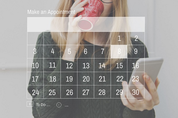Woman drinking from cup whilst looking at screen with appointment calendar