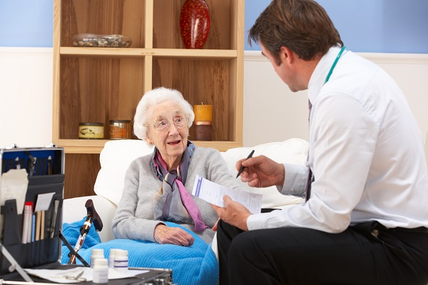 Male Gp seeing an elderly woman at home
